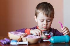 Leuk weinig jongen die met veelkleurige plasticine spelen Jongen het spelen met speelgoed Tandhulpmiddelen Grappig gezicht Het po royalty-vrije stock fotografie