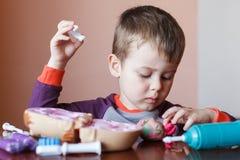 Leuk weinig jongen die met veelkleurige plasticine spelen Jongen het spelen met speelgoed Tandhulpmiddelen Grappig gezicht Het po stock afbeeldingen