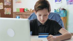 Leuk is weinig jongen die online gebruikend ingaand creditcardaantal die laptop computer met behulp van en gelukkig na het maken  stock footage
