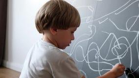 Leuk weinig jongen die op bord trekken Kind van basisschool Het concept van het onderwijs Terug naar School stock video