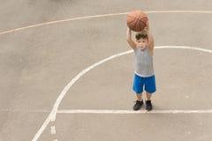 Leuk weinig jongen die op een basketbalhof praktizeren Stock Foto's