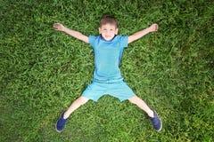 Leuk weinig jongen die op groen gras liggen Royalty-vrije Stock Fotografie