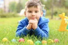 Leuk weinig jongen die op groen gras in park liggen Stock Foto