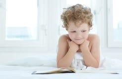Leuk weinig jongen die op het boek van de bedlezing thuis liggen Royalty-vrije Stock Afbeeldingen