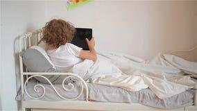 Leuk weinig jongen die op zijn bed ontspannen die de digitale spelen van de tabletcomputer spelen stock videobeelden