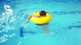 Leuk weinig jongen die opblaasbare ring in de pool gebruikt stock video