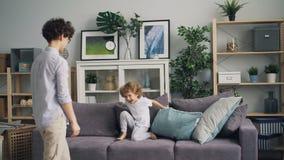 Leuk weinig jongen die pret met hoofdkussenstrijd hebben met zijn moeder op bank thuis stock footage