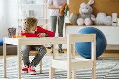 Leuk weinig jongen die rode sweaterzitting draagt bij kleine houten lijst royalty-vrije stock afbeelding