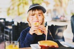 Leuk weinig jongen die sandwich voor ontbijt eten Royalty-vrije Stock Foto's