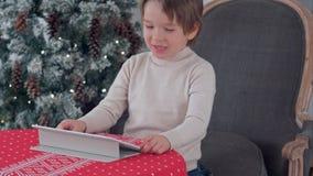 Leuk weinig jongen die tablet gebruiken terwijl het zitten op een grote leunstoel thuis over Chirstmas-boomachtergrond stock foto's