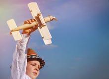 Leuk weinig jongen die zijn stuk speelgoed tweedekker vliegen Royalty-vrije Stock Afbeeldingen