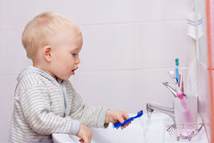 Leuk weinig jongen die zijn tanden schoonmaakt stock fotografie