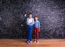 Leuk weinig jongen en meisje voor een groot bord Royalty-vrije Stock Foto's