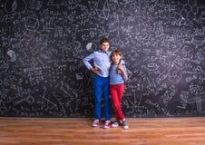Leuk weinig jongen en meisje voor een groot bord Royalty-vrije Stock Afbeeldingen