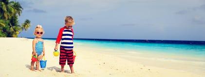 Leuk weinig jongen en peutermeisjesspel met zand op strand Stock Foto