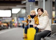 Leuk weinig jongen en zijn grootmoeder/moeder het wachten sneltrein op stationplatform stock afbeelding