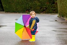 Leuk weinig jongen in gele rubberlaarzen met kleurrijke regenboogparaplu die op natte weg blijven die camera bekijken Na Regen stock afbeelding