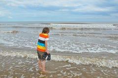 Leuk weinig jongen in golven op strand, koud water Stock Foto's