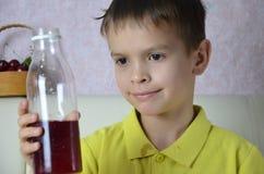 Leuk weinig jongen het drinken sap thuis, de dranken van het kersensap van een fles of een glas met een stro stock fotografie