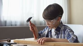 Leuk weinig jongen het hameren spijker in houten plank, hobby en vrije tijd, workshop stock video