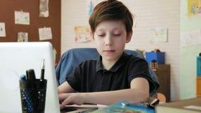 Leuk weinig jongen het schrijven poging voor school in zijn ruimte die thuiswerk doen stock videobeelden