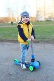 Leuk weinig jongen (3 jaar) met autoped openlucht Stock Foto's