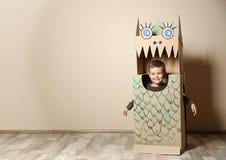 Leuk weinig jongen in kartonkostuum van dinosaurus dichtbij kleurenmuur stock afbeelding