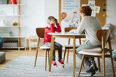 Leuk weinig jongen met ADHD tijdens zitting met professionele therapeut stock foto's
