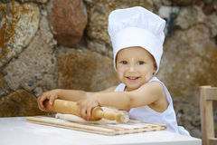 Leuk weinig jongen met chef-kokhoed Stock Foto