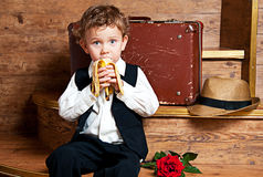 Leuk weinig jongen met een banaan in zijn handzitting Stock Afbeeldingen