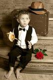 Leuk weinig jongen met een banaan in zijn handzitting Royalty-vrije Stock Afbeeldingen