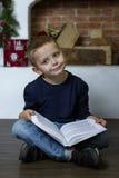 Leuk weinig jongen met een boek Stock Afbeeldingen