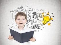 Leuk weinig jongen met een boek, bedrijfsidee royalty-vrije stock foto's