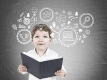 Leuk weinig jongen met een boek, bedrijfsstrategie stock foto