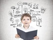Leuk weinig jongen met een boek, businessplan stock afbeelding