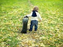 Leuk weinig jongen met een grote koffer Stock Foto's