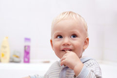 Leuk weinig jongen met een vinger in zijn mond stock fotografie