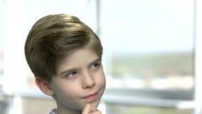 Leuk weinig jongen met nadenkende uitdrukking stock videobeelden