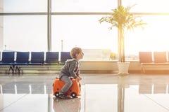 Leuk weinig jongen met oranje koffer bij luchthaven royalty-vrije stock foto