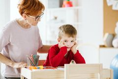 Leuk weinig jongen met problemen tijdens vergadering met therapeut stock foto's