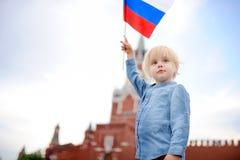 Leuk weinig jongen met Russische vlag met Spasskaya-toren Rusland, Moskou op achtergrond royalty-vrije stock afbeeldingen