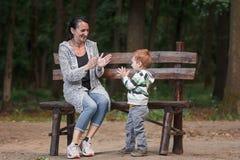 Leuk weinig jongen met zijn moederzitting op een bank Royalty-vrije Stock Foto's