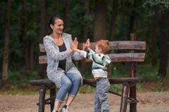 Leuk weinig jongen met zijn moederzitting op een bank Stock Foto
