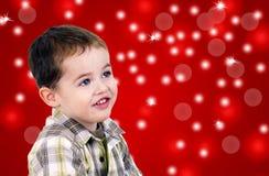 Leuk weinig jongen op rode achtergrond met lichten Royalty-vrije Stock Foto's