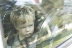 Leuk weinig jongens dicht omhooggaand portret door het autoraamglas Royalty-vrije Stock Foto