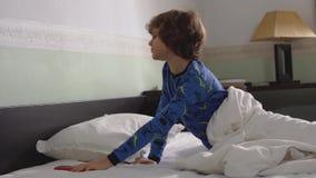 Leuk weinig jongensontwaken in de ochtend met slordig haar en het dragen van pyjama Omhoog zo slaperige kind het kielzog en krijg stock video