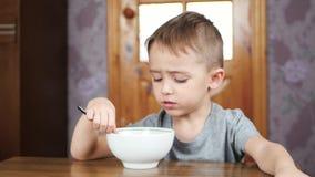 Leuk weinig jongenszitting bij de lijst en het eten van soep met eetlust Voeding en gezondheid van kinderen stock footage