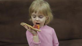Leuk weinig Kaukasisch meisje die pizza eten Hongerig kind die een beet van pizza nemen stock video