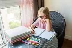 Leuk weinig Kaukasisch meisje die thuiswerk doen en een document schrijven Het jonge geitje geniet van thuis lerend met geluk Sli royalty-vrije stock foto's