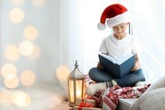 Leuk weinig kind in het verhaal van de lezingskerstmis van de Kerstmanhoed royalty-vrije stock foto